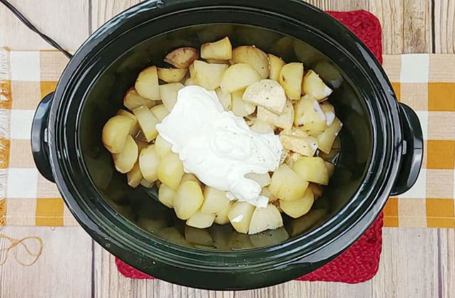 Cooked potatoes, sour cream, and seasonings in a Crockpot
