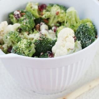 Broccoli Cauliflower salad in a white mixing bowl