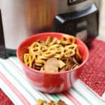 Crockpot Chex Mix in a red bowl in front of a stainless steel crockpot