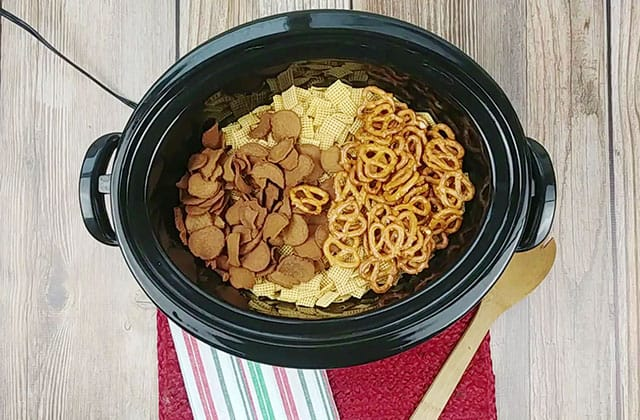 Chex cereal, bagel chips, and pretzels in a Crockpot
