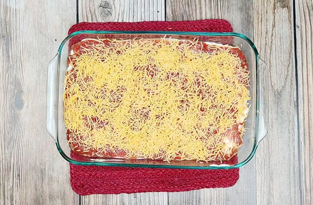 Taco dip recipe in a glass baking dish ready to be baked in the oven