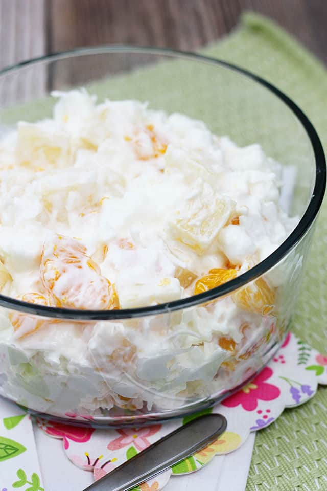 Ambrosia salad in a clear glass bowl on a floral napkin