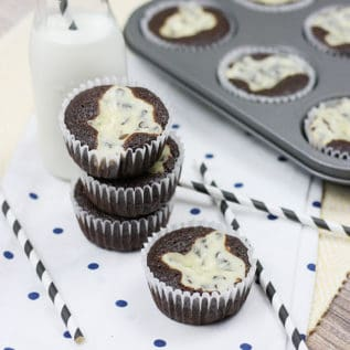 Black bottom cupcakes stacked next to a bottle of milk with a cupcake tin in the background