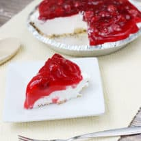 No bake cherry cheesecake slice on a white plate in front of the whole pie in the background