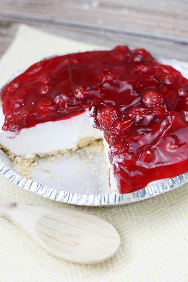 No Bake Cherry Cheesecake in a pie tin on a yellow placemat with a slice taken out of the pie