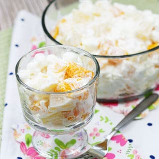 Ambrosia salad in a glass dessert dish with a fork next to it
