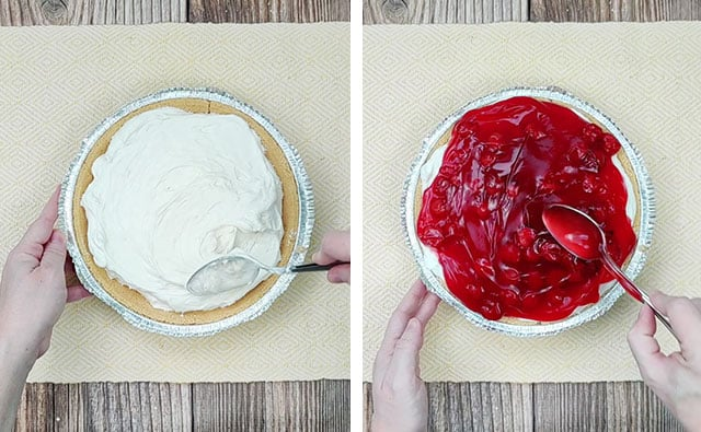 Spreading cheesecake filling into a graham cracker crust and topping it with cherry pie filling