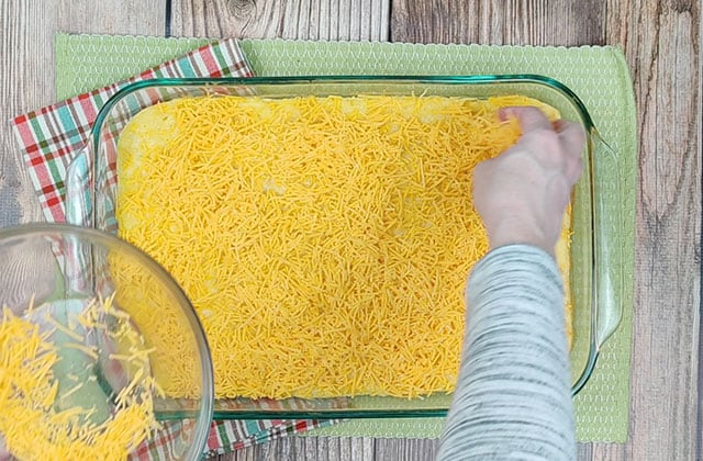 Adding shredded cheese to the top of the corn souffle