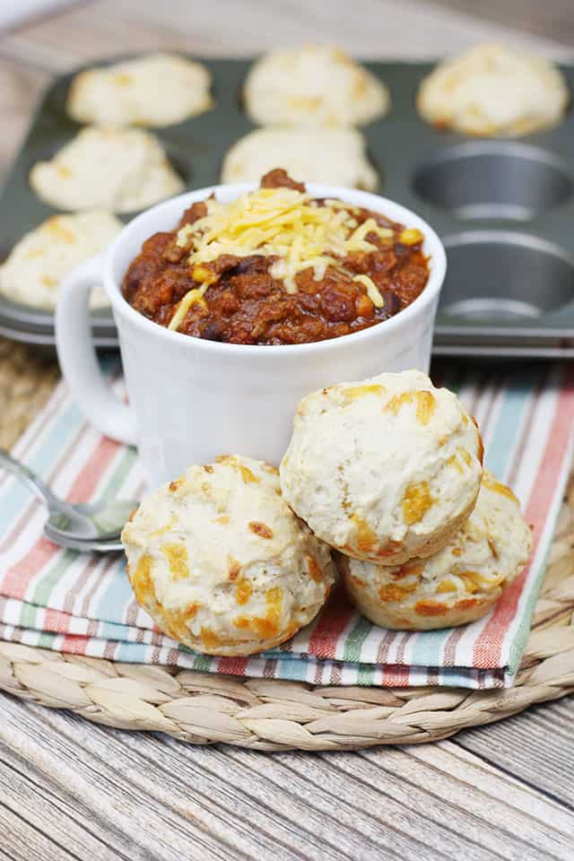 Beer bread muffins stacked next to a bowl of chili on a placemat