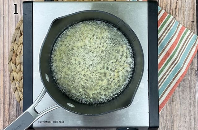 Minced garlic and melted butter in a saucepan on a stovetop