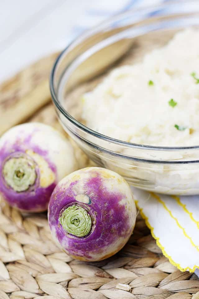 Two purple topped turnips next to a glass bowl of mashed turnips