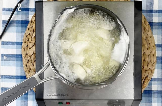 Chopped turnips and potatoes in boiling water in a pan on the stove