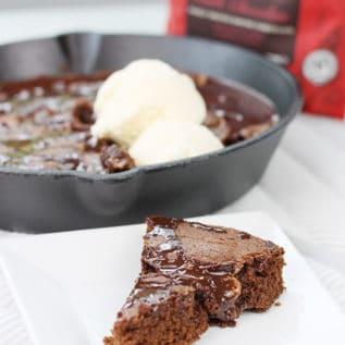 A slice of the brownie skillet on a white square plate with the cast iron skillet in the background