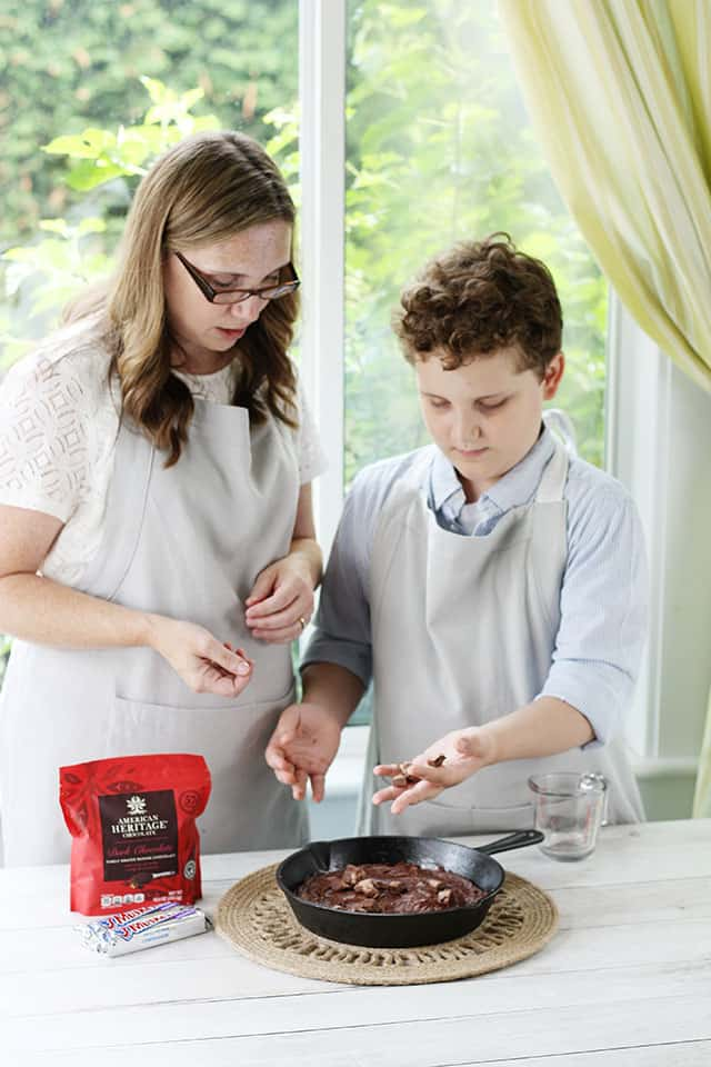 A son stirring in chopped candy bars into brownie batter in a glass bowl